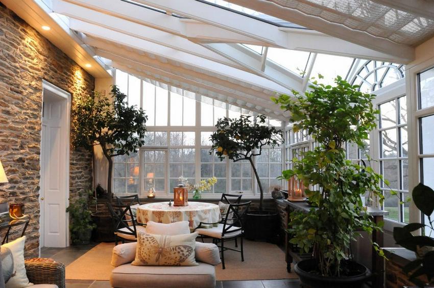 На фото пример красивого и практичного остекления зимнего сада, где можно выращивать цитрусовые и другие деревья