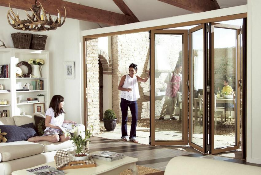 Удобным способом остекления входной стены является установка окон, которые складываются гармошкой