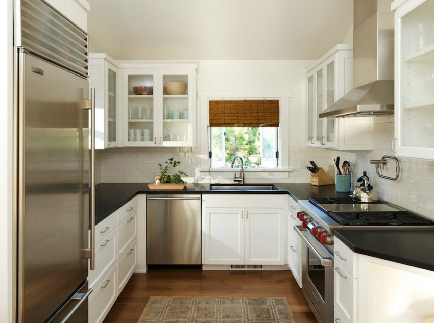 Белые классические фасады кухни красиво сочетаются с металлическими поверхностями кухонной техники