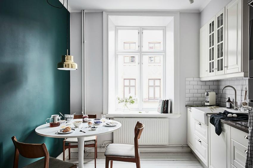 Покрытие одной из стен яркой матовой краской придаст глубину маленькой кухне