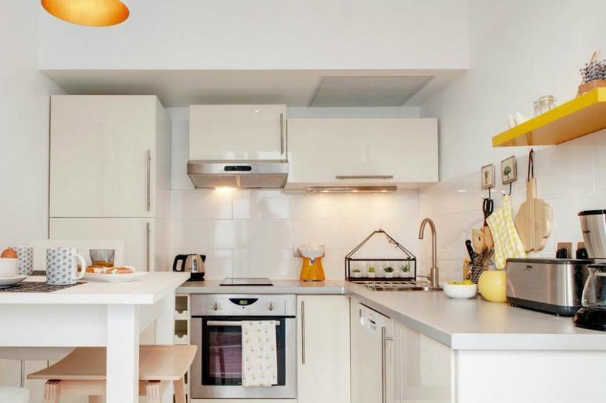 Благодаря белому цвету кухни, который отражает и рассеивает свет, можно не устанавливать много дополнительных предметов освещения