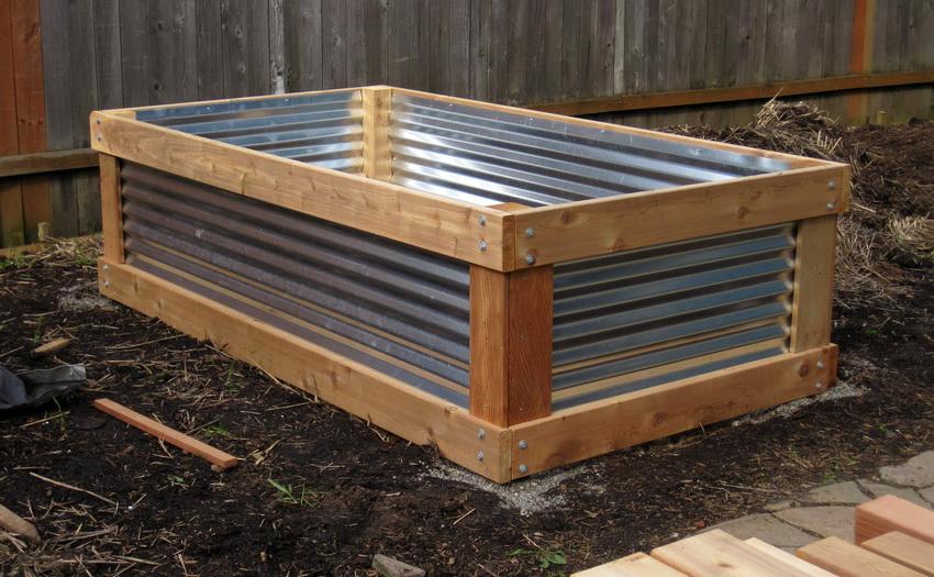 Деревянный каркас служит удобным вместилищем для металлических стенок грядки