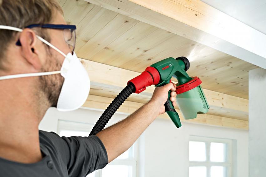 Покрасить потолок очень быстро и без особых усилий можно, используя краскопульт, но перед этим стоит закрыть все поверхности защитной пленкой