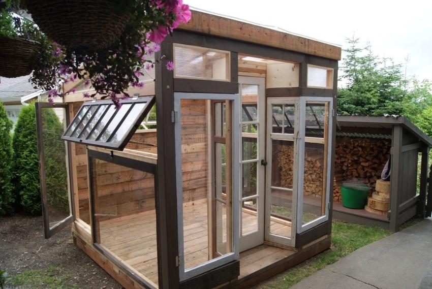Строительство высокой теплицы из старых окон и дверей позволяет установить удобные полки для выращивания как низких, так и высокорослых растений