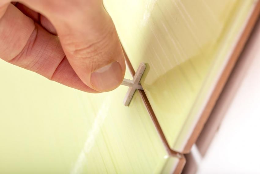 При работе с плиткой необходимо пользоваться специальными крестиками, которые помогут контролировать ширину швов и высоту укладки каждого элемента