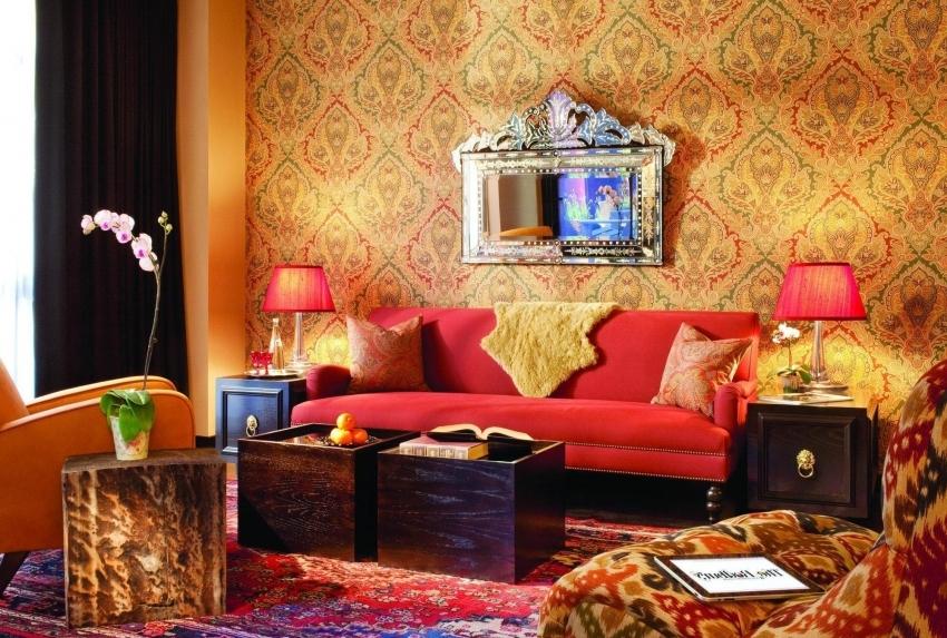 Восточный стиль в оформлении гостиной предполагает использование обоев теплых оттенков с золотым или красным орнаментом
