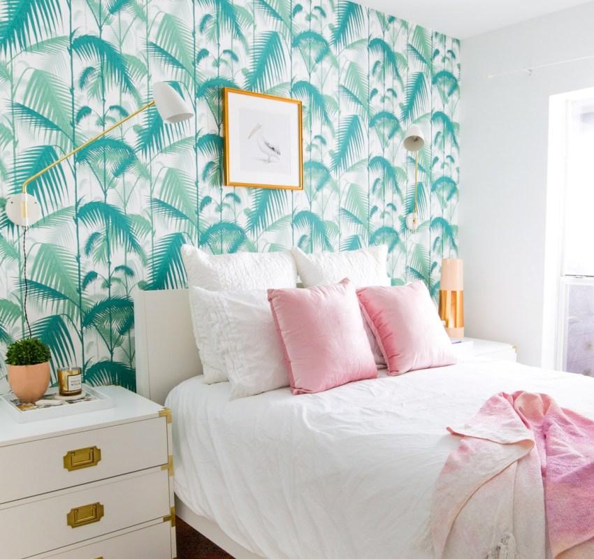 Одна из стен белой спальни оклеена яркими зелеными обоями