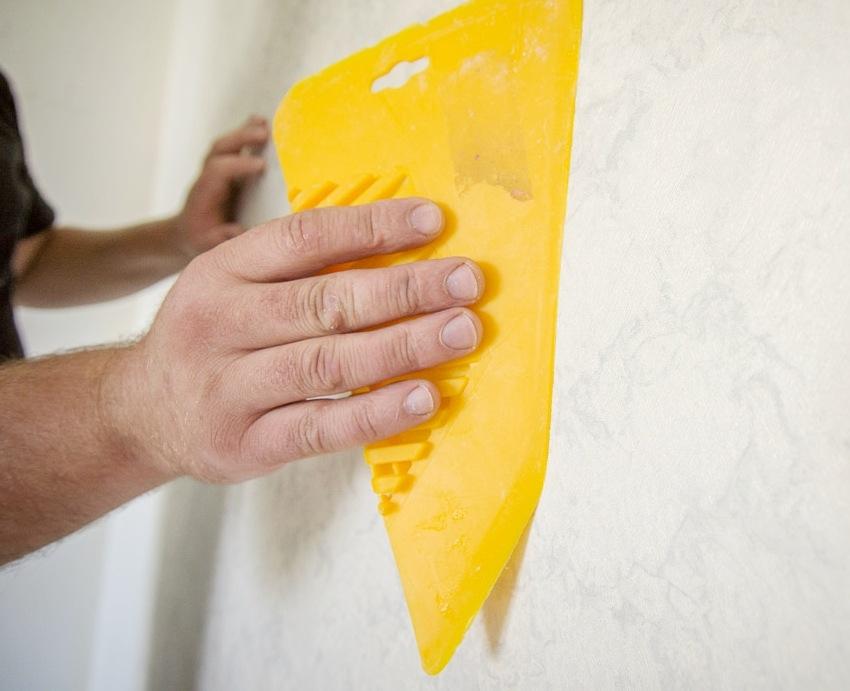 После приклеивания полотна обоев к стене необходимо избавиться от пузырей воздуха специальным шпателем