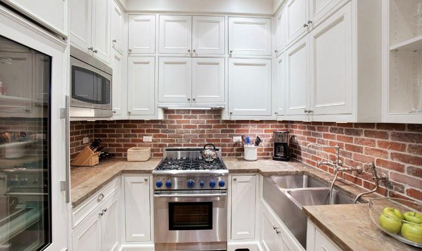 Кирпичная кладка в сочетании с белой кухонной мебелью выглядит эффектно