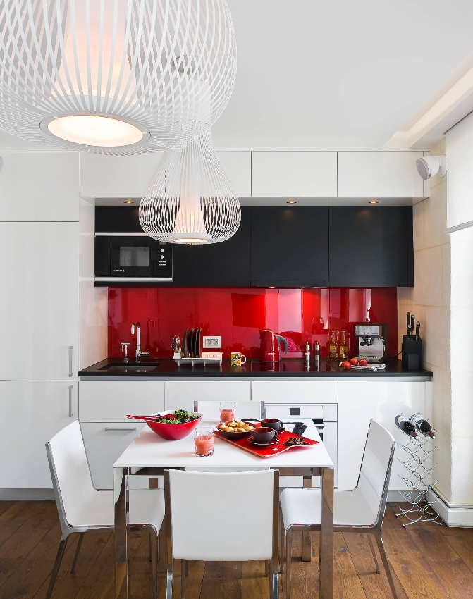 Стильная панель красного цвета способна создать необычный эффект контраста при грамотном комбинировании с бело-черной мебелью кухни