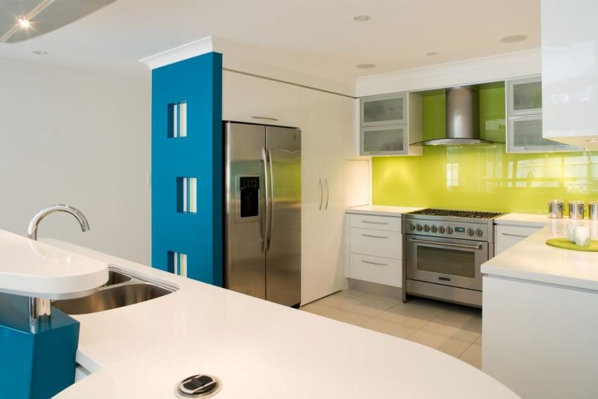 Стеклянные панели гораздо гармоничнее смотрятся в интерьере кухонь в современном стиле, так как идеально сочетаются с фасадами гарнитура, а также с хромированными элементами бытовой техники