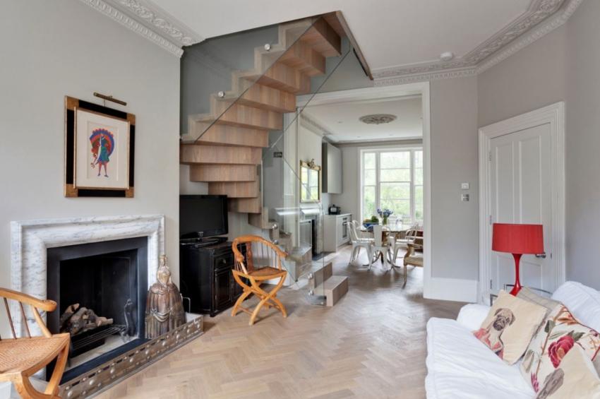 Самым популярным вариантом расположения камина в гостиной является его установка напротив дивана