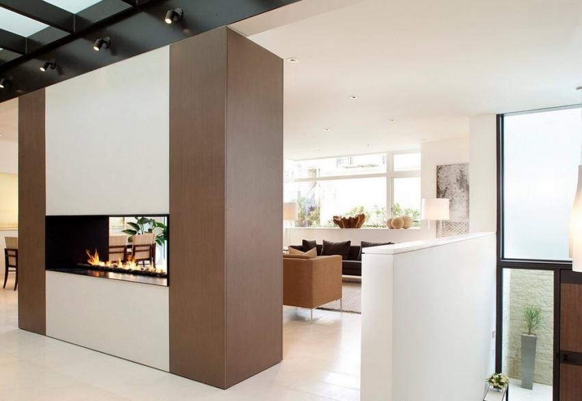 Перегородка с камином может использоваться для зонирования комнаты-студии