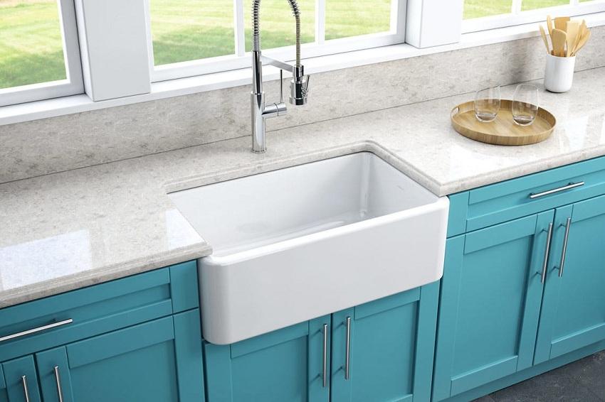 Кухонная мойка из керамики традиционного белого цвета отлично гармонирует с голубыми фасадами