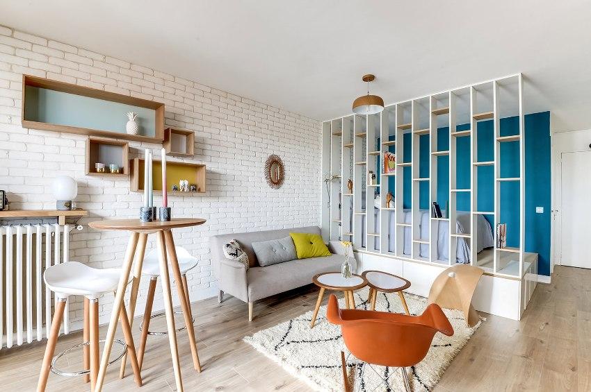 В образовавшейся путем зонирования спальне может разместиться полноценная двуспальная кровать со столом и диваном для отдыха