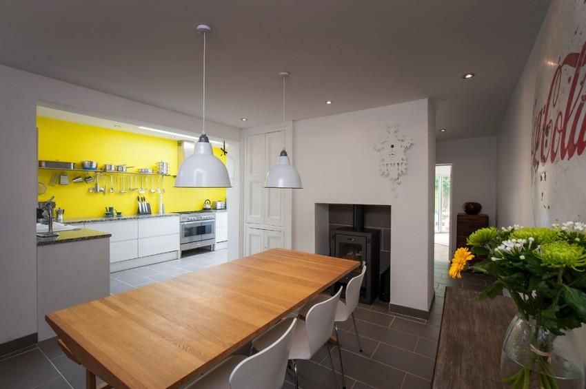 Кухонный фартук оформлен ярким желтым закаленным стеклом и рейлинговой системой для хранения
