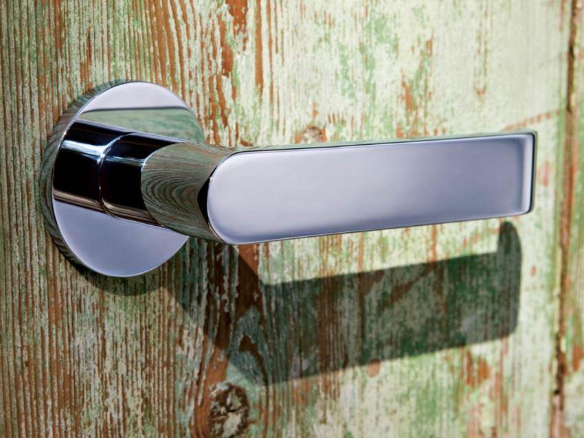 Хромированная дверная ручка эффектно выделяется на фоне двери из брашированной древесины