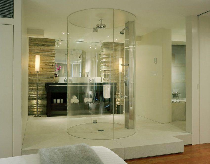 Круглое душевое ограждение расположено на подиуме в просторной ванной