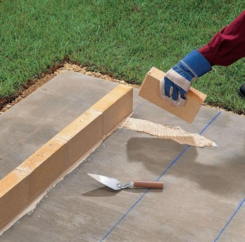 Lay the first row of bricks on the previously cleaned foundation at a distance of 10-20 cm from its edge