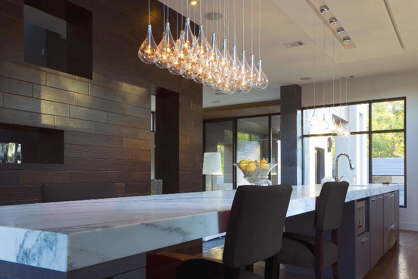 Коричневые панели на стене хорошо гармонирует со светлой мебелью кухни