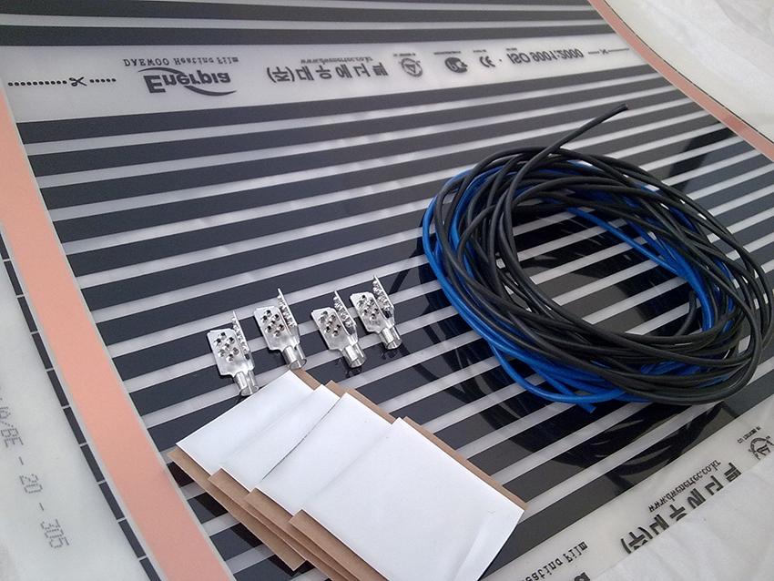 Упаковка с теплым пленочным полом содержит термопленку, изоляцию, проводку и контактные зажимы