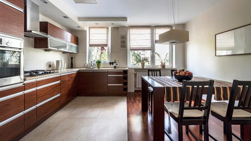 Рабочая зона кухонного пола облицована практичной керамикой, а обеденная выложена ламинатом