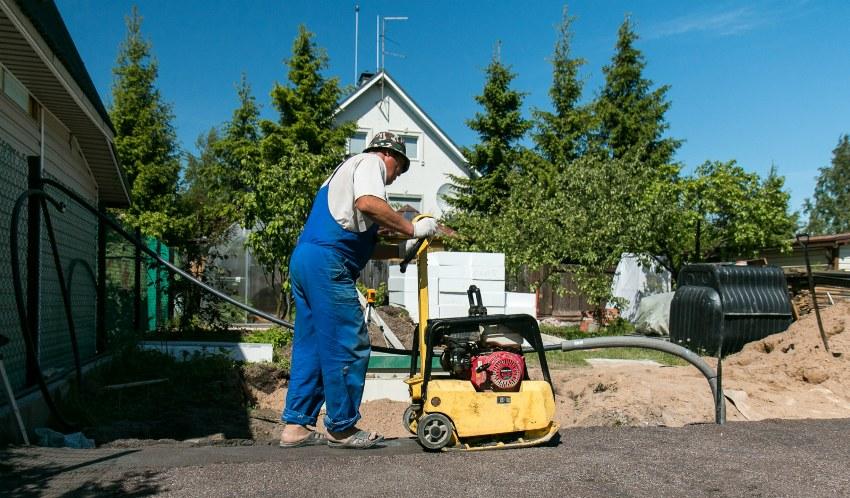 Прежде чем заливать бетон, необходимо подготовить ровную площадку и как следует утрамбовать её специальной машиной