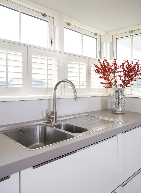 Для кухни лучше выбирать жалюзи из пластика или металла, так как за ними легче ухаживать, и они не впитывают запахи
