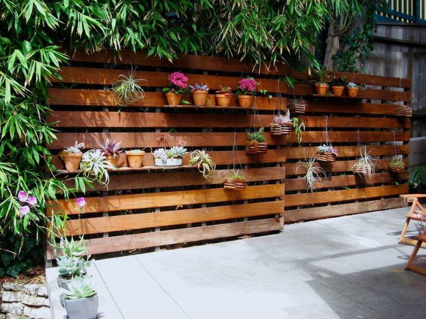 Забор на дачном участке построен из поддонов и дополнен полками для горшков с цветами