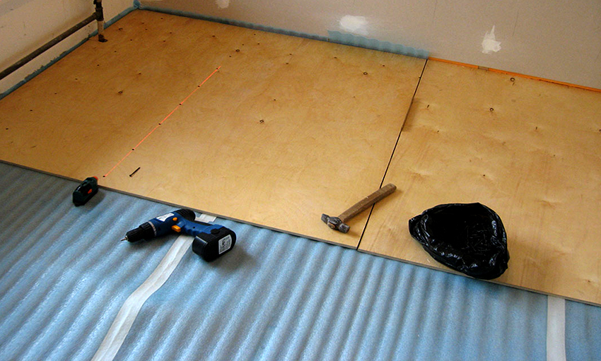 На деревянный пол лучше всего стелить фанеру, толщина которой должна быть минимум 7 мм