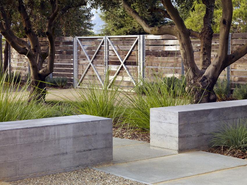Изгородь из бетона проста в исполнении и часто используется на участках с современным дизайном