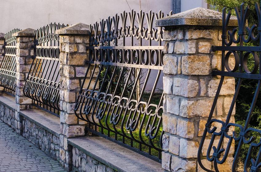 Использование кованых секций забора и основания из камня - весьма популярный вариант ограждения