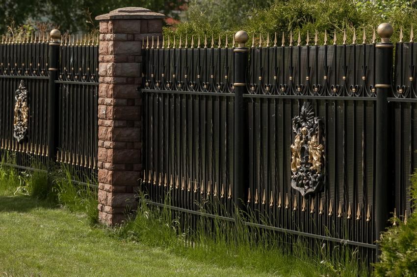 Кованый забор с профнастилом позволяет закрыть территорию от посторонних глаз, сохранив внешний вид заграждения