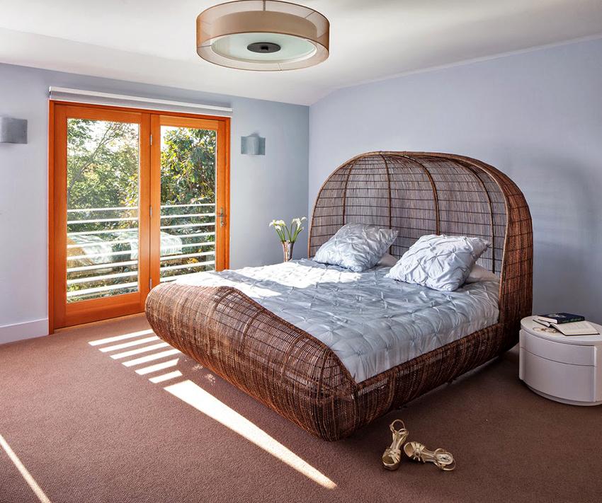 Кровать необычной формы, изготовленная из натурального ротанга, станет главным украшением спальни