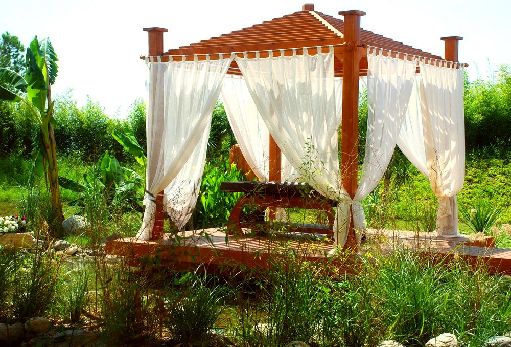 Чтобы беседка-пергола стала более уютной ее можно декорировать легкими шторами