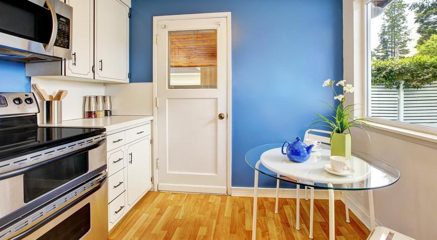 Стол со стеклянной столешницей придает дизайну интерьера кухни легкости и изящества