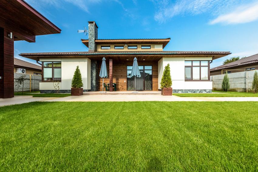 Простоту и элегантность домам в стиле модерн можно придать за счет использования дерева для отделки фасада