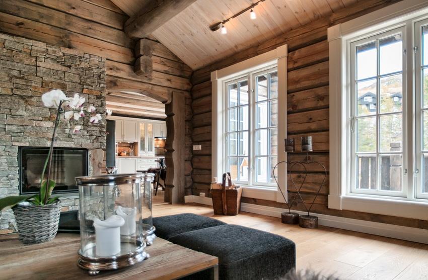 В домах из бруса или бревна популярный вариант дизайна интерьера с минимальной отделкой