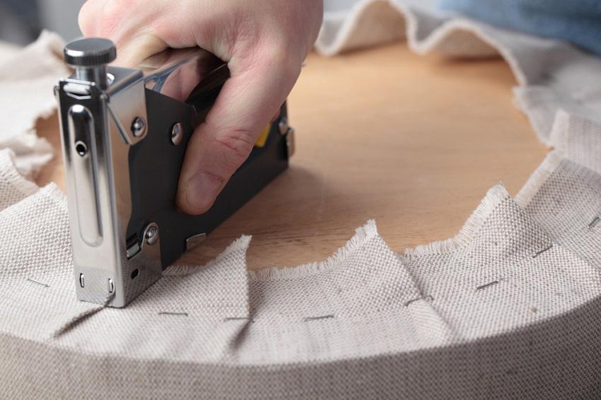 Ткань закрепляется с нижней стороны сиденья с помощью степлера и скоб