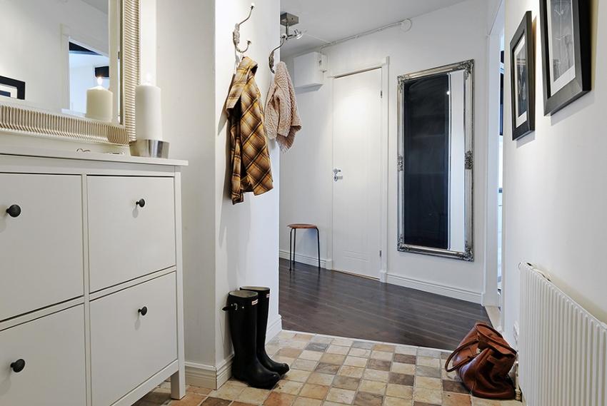 Увеличить прихожую можно с помощью зонирования помещения, применяя два вида напольного покрытия