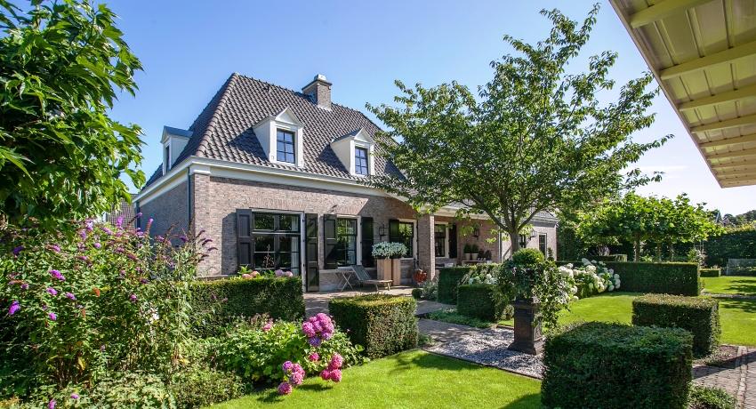Фасады домов в английском стиле чаще всего увиты плющом, клумбы с деревьями и кустарниками разбросаны по всему участку