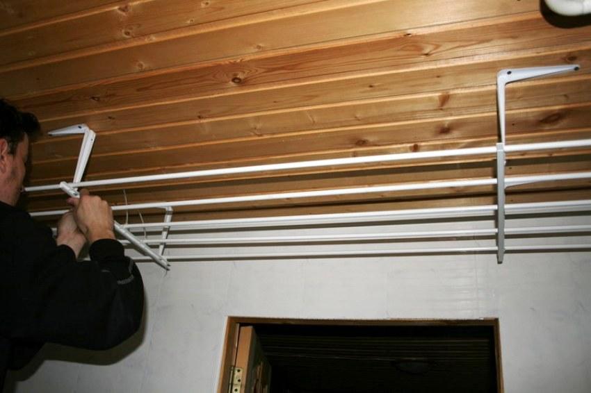 Штанга подтягивается вверх и крепится с помощью фиксатора на стену
