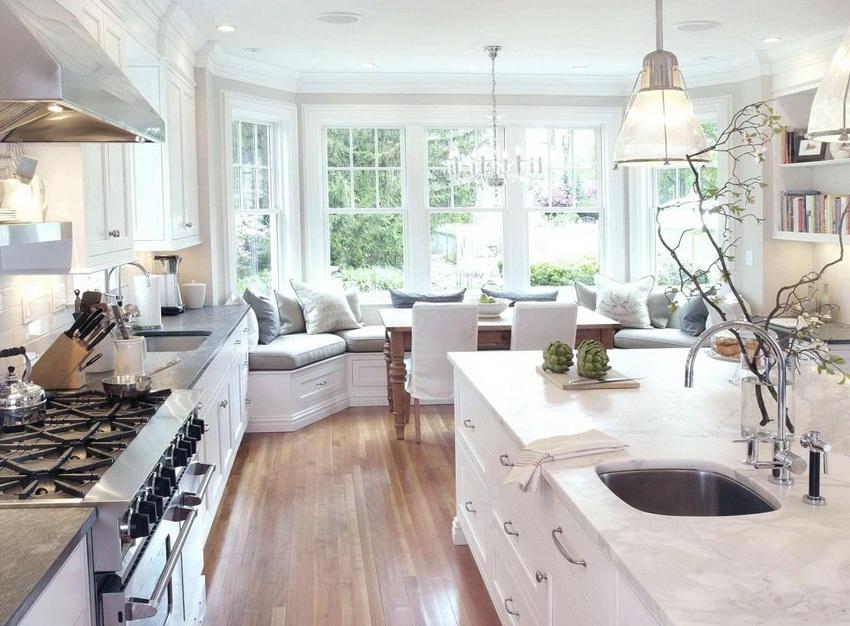 Классика в интерьере кухни отражается в светлом текстиле и изящных линиях мебели и декора