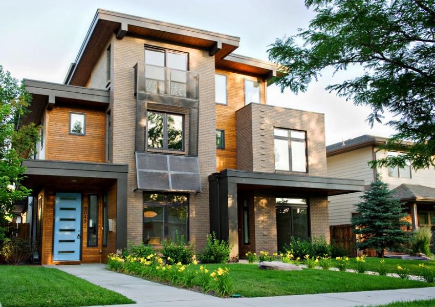 Для оформления фасада кирпичного коттеджа в стиле модерн сочетаются плавность линий со сложными, в архитектурном плане, решениями
