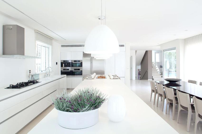 Стиль минимализм в интерьере кухни позволяет обустроить столовую с гостиной, а зонировать можно с помощью света и цвета