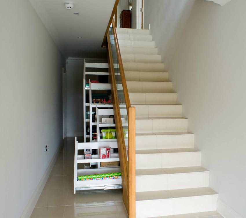 Если лестница довольно широкая, то лучше устанавливать шкаф с конструкцией из выдвижных ящиков