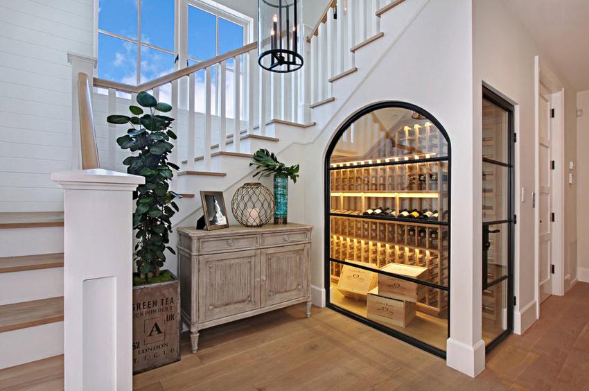 Наличие стекла в шкафе под лестницей препятствует оседанию пыли на полках и выступает элементом эффектного дизайна