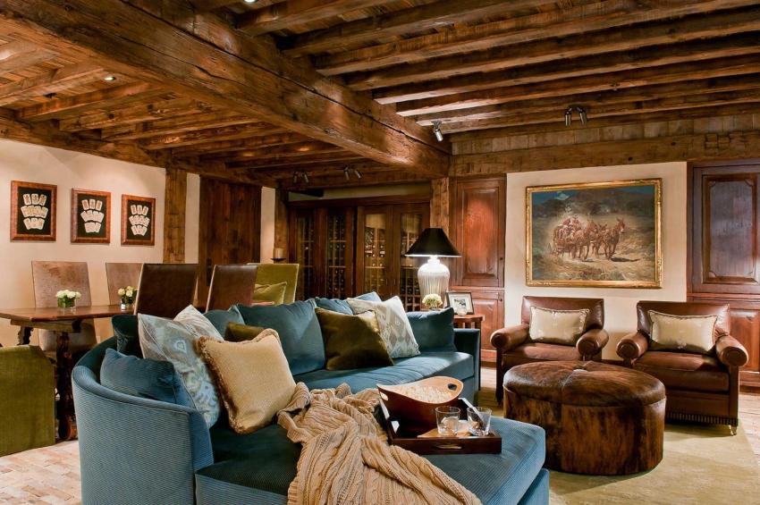Камин и потолок оформленный деревянными балками являются главными чертами гостиной в стиле кантри