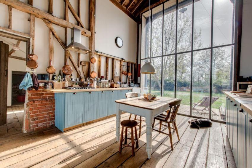 Потолочное полотно в интерьере кухни в стиле прованс традиционно оформляется деревянными балками