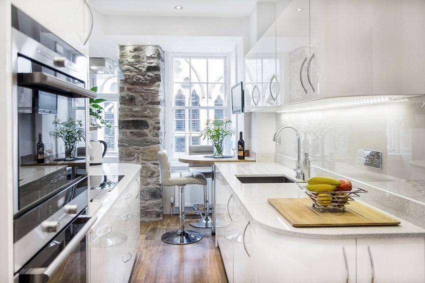 Белый кухонный гарнитур с глянцевой поверхностью создаст ощущение легкости на тесной кухне